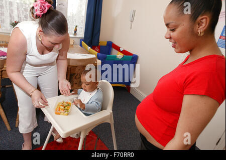 Pregnant young woman watching her friend feeding her baby in a high chair, - Stock Photo
