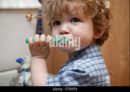Baby boy learning to clean his own teeth, - Stock Photo