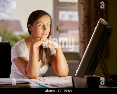 Woman sitting next to a lightbox for relaxation - Stock Photo
