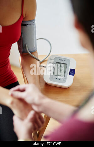 Doctor taking patients bloody pressure - Stock Photo