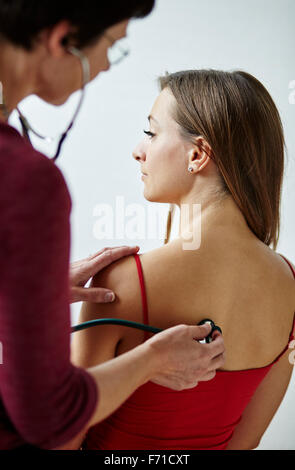Doctor listening to patients back and chest - Stock Photo