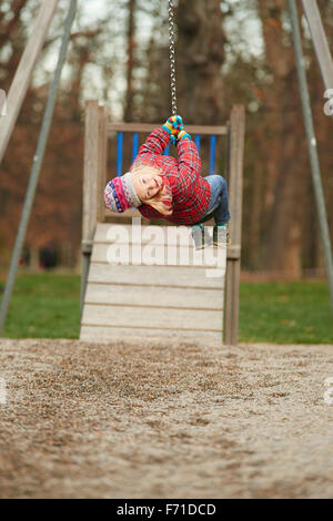 Child girl rids on Flying Fox play equipment in a children's playground. Seesaw, sliding, flying, rope slide - Stock Photo