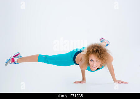 Portrait of a fitness woman doing handstand exercise isolated on a white background - Stock Photo
