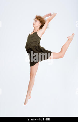 Full length portrait of a young woman dancing isolated on a white background - Stock Photo
