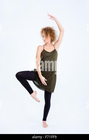 Full length portrait of a young woman with curly hair dancing isolated on a white background - Stock Photo