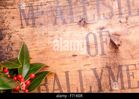 Holly on old wooden crate - Stock Photo