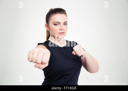 Portrait of a fat woman in sports wear hitting at camera isolated on a white background - Stock Photo