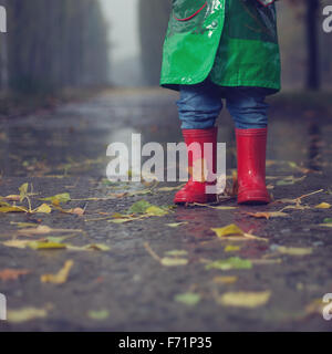 Baby walking in autumn rainy park - Stock Photo