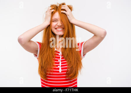 Funny amusing cheerful girl with messy tousled long red hair holding her hands to her head and laughing - Stock Photo