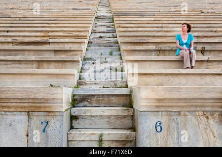 Tourist sitting on seats in the Panathenaic Stadium, original modern day Olympic Stadium, Athens, Greece - Stock Photo