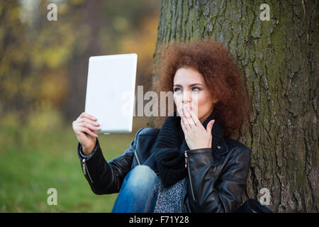 Portrait of a young woman making selfie photo on tablet computer or making video call outdoors - Stock Photo