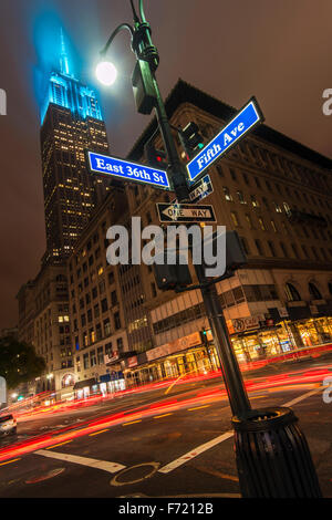 Night low angle view of the Empire State Building with teal color lights, Manhattan, New York, USA - Stock Photo