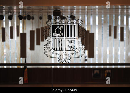 The coat-of-arms of the tiny Principality of Andorra on a clear glass inside the parliament building. - Stock Photo