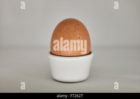 A brown hen's egg in an egg cup - Stock Photo