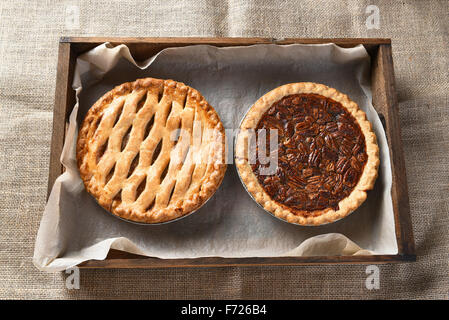 High angle view of an apple pie and pecan pie in a wood box lined with parchment paper. Horizontal format on a burlap - Stock Photo