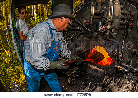 The fireman stokes the fire in the boiler of the steam engine, Cumbres & Toltec Scenic Railroad train on the 64 - Stock Photo