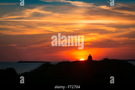 A meditating man watches the sun setting at the coast, in front of a colourful sky with clouds - Stock Photo