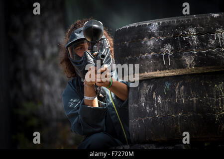 A photograph of a paintball player girl at work. Portrait d'une jeune joueuse de paintball en action. - Stock Photo