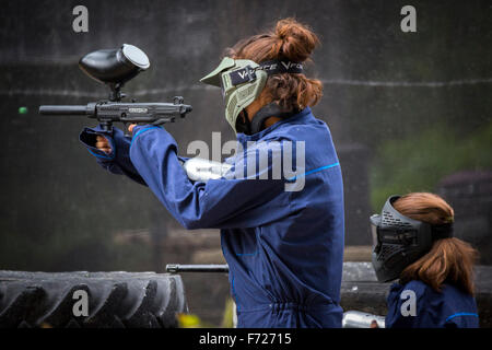 Paintball player girls at work. Jeunes joueuses de paintball en action. - Stock Photo