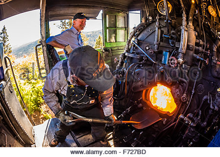 The fireman stokes the fire in the boiler of the steam engine (Colorado Governor John Hickenlooper sits behind), - Stock Photo