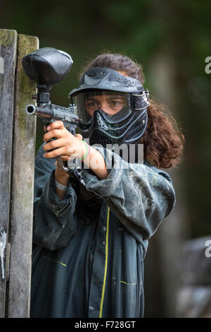 Portrait of a paintball player girl at work. Portrait d'une jeune joueuse de paintball en action. - Stock Photo