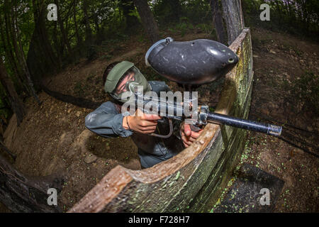 A paintball player girl at work. Jeune fille joueuse de paintball en action. - Stock Photo