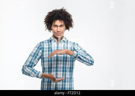 Portrait of a happy casual afro american man holding something invisible isolated on a white background - Stock Photo