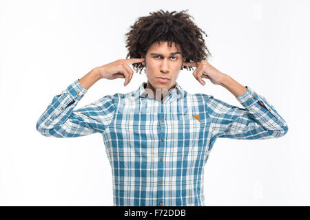 Portrait of a young serious afro american man covering his ears isolated on a white background - Stock Photo