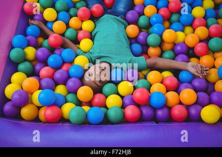 Cute smiling boy in sponge ball pool - Stock Photo