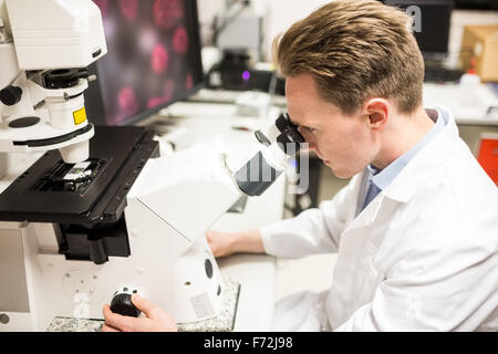 Scientist looking through a microscope - Stock Photo