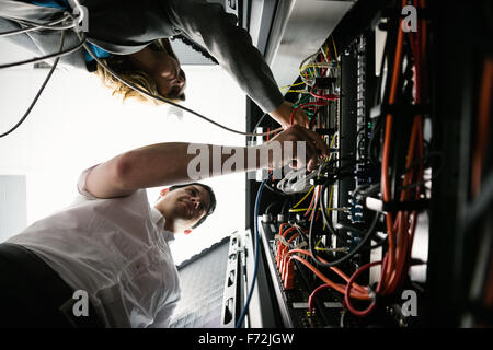 Team of technicians working together on servers - Stock Photo