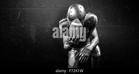 Composite image of upset american football player kneeling while holding ball - Stock Photo
