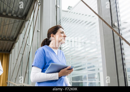 Nurse using her tablet pc - Stock Photo