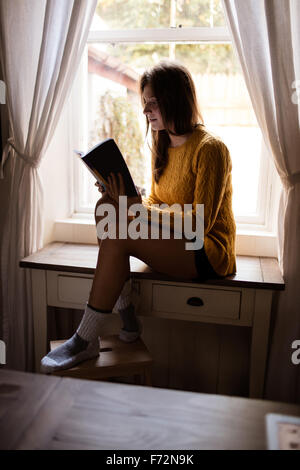Young woman sitting on table studying - Stock Photo