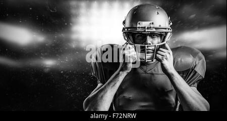 Composite image of portrait of american football player holding helmet - Stock Photo