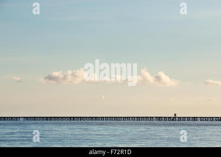 People from the Bajo village on the Togean Islands crossing the bridge to the mainland, Indonesia. - Stock Photo