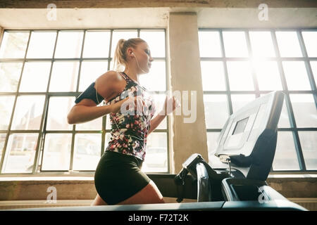 Side view of female in action exercising in health club. Fit young woman running on treadmill in the gym. - Stock Photo