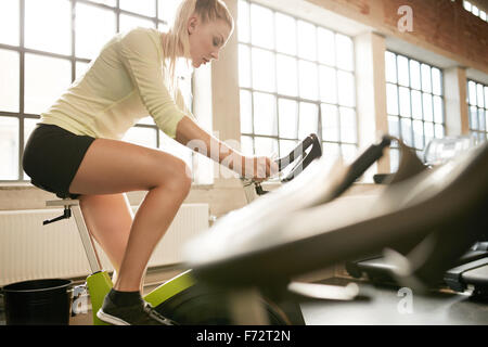 Fit woman working out on exercise bike at the gym. Focused young female exercising on bicycle in health club. - Stock Photo