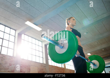 Fitness woman preparing to practice deadlift with heavy weights in gym. Female doing heavy weight lifting work out - Stock Photo