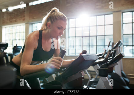 Fit woman working out on exercise bike at the gym. Indoor shot of a female doing fitness training on spinning bicycle - Stock Photo
