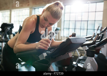 Fitness woman on bicycle doing cardio workout at gym. Fit young female exercising on gym bike. - Stock Photo
