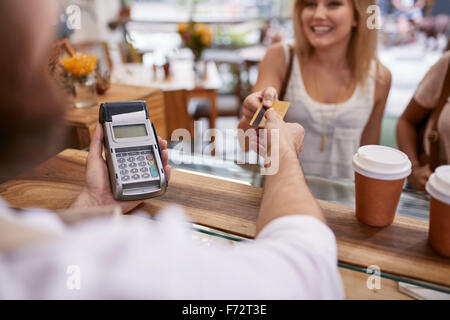 Customer paying for their order with a credit card in a cafe. Bartender holding a credit card reader machine and - Stock Photo