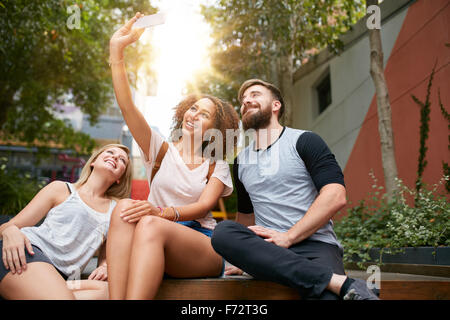 Group of smiling friends taking selfie with smart phone. Multiracial man and women enjoying themselves outdoors - Stock Photo