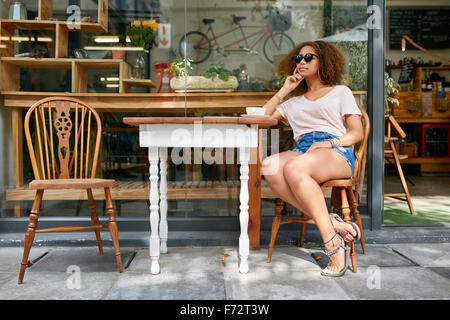 Portrait of stylish young woman sitting alone outdoors at sidewalk cafe looking away and thinking. Young african - Stock Photo