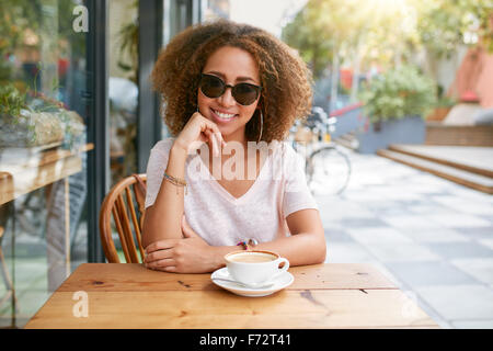 Portrait of attractive young woman sitting at outdoor coffee shop with a cup of coffee. African young stylish girl - Stock Photo