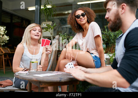 Group of young people sitting at the table and playing cards. Friends playing card game while sitting at outdoor cafe. Stock Photo