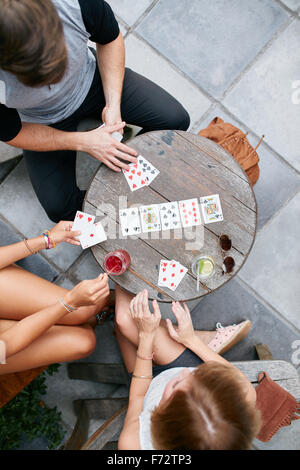Three young friends playing cards at cafe. Directly above shot of young man and women sitting around an outdoors - Stock Photo