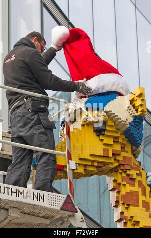 Berlin, Germany. 24th Nov, 2015. A worker puts a red Santa hat on a giraffe built out of Lego bricks in front of - Stock Photo