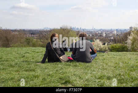 A couple Relaxing and enjoying the view from Parliament hill in Hampstead Heath of the London Skyline - Stock Photo