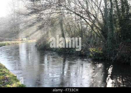 Early morning on the Monmouthshire Brecon canal.The water is frozen and sunlight filters through the mist. - Stock Photo